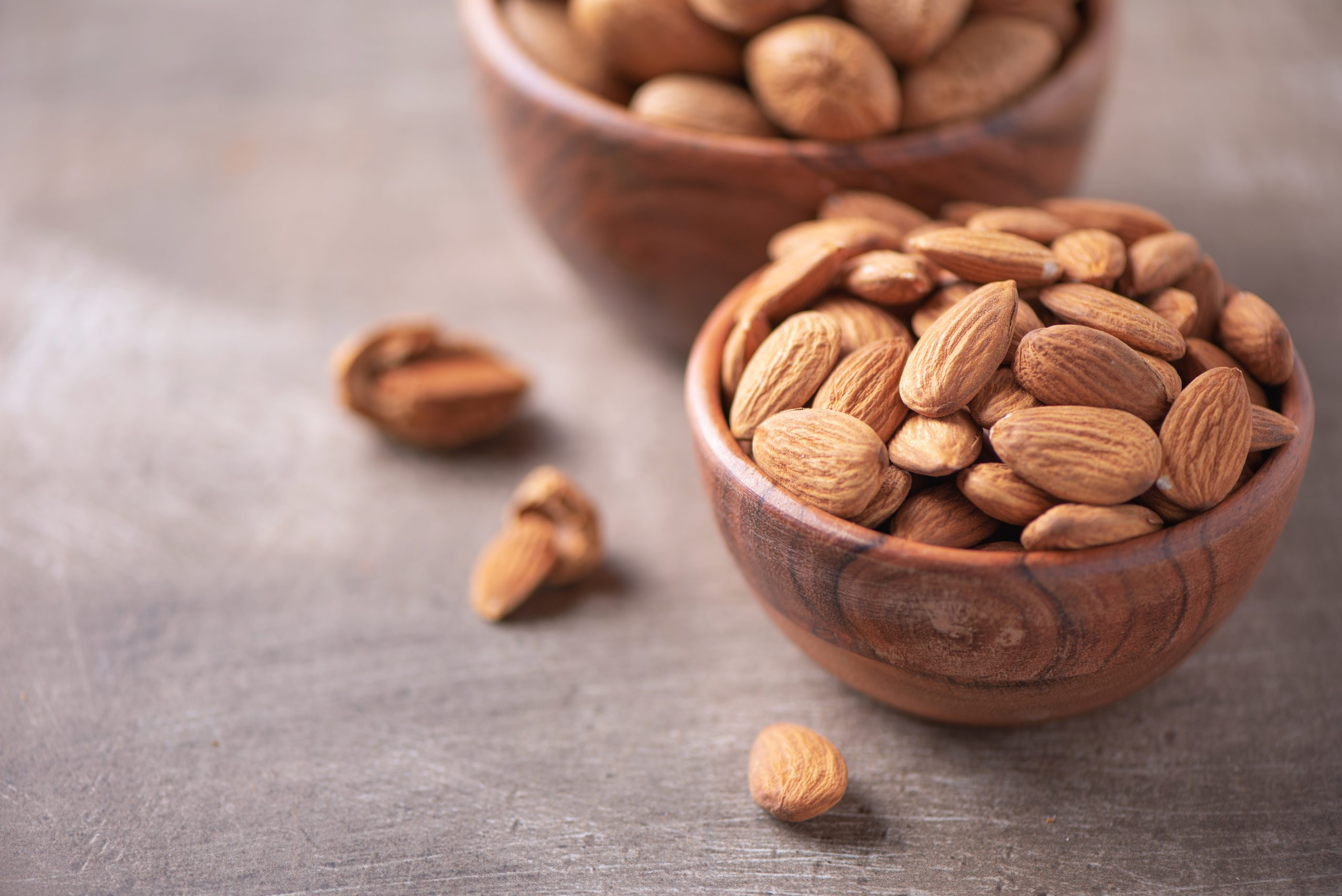 Almond nuts in wooden bowl on wood textured background. Copy space. Superfood, vegan, vegetarian food concept. Macro of almond nut texture, selective focus. Healthy snack