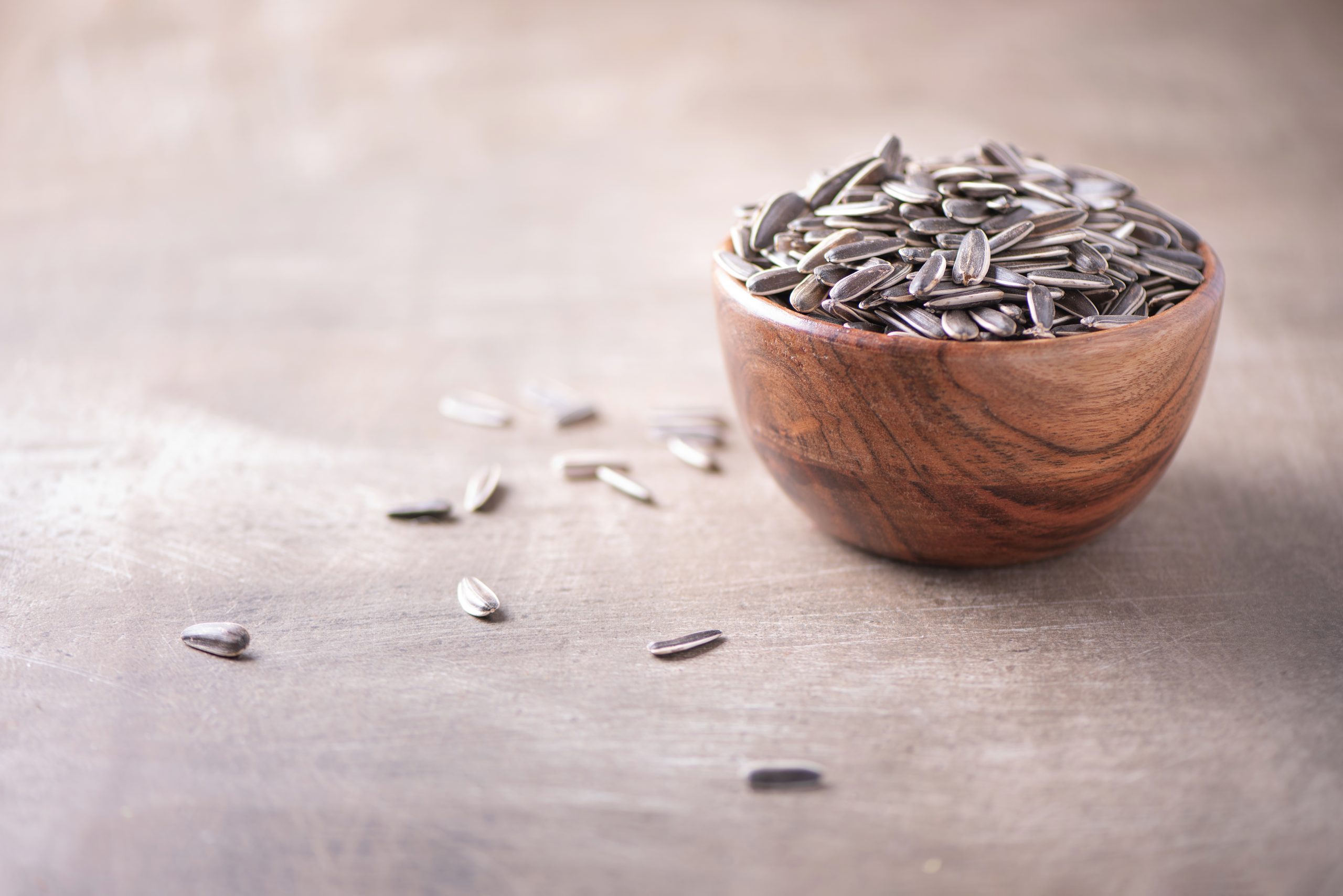 Sunflower seeds in wooden bowl on wood textured background. Copy space. Superfood, vegan, vegetarian food concept. Macro of sunflower seeds, selective focus. Healthy snack.