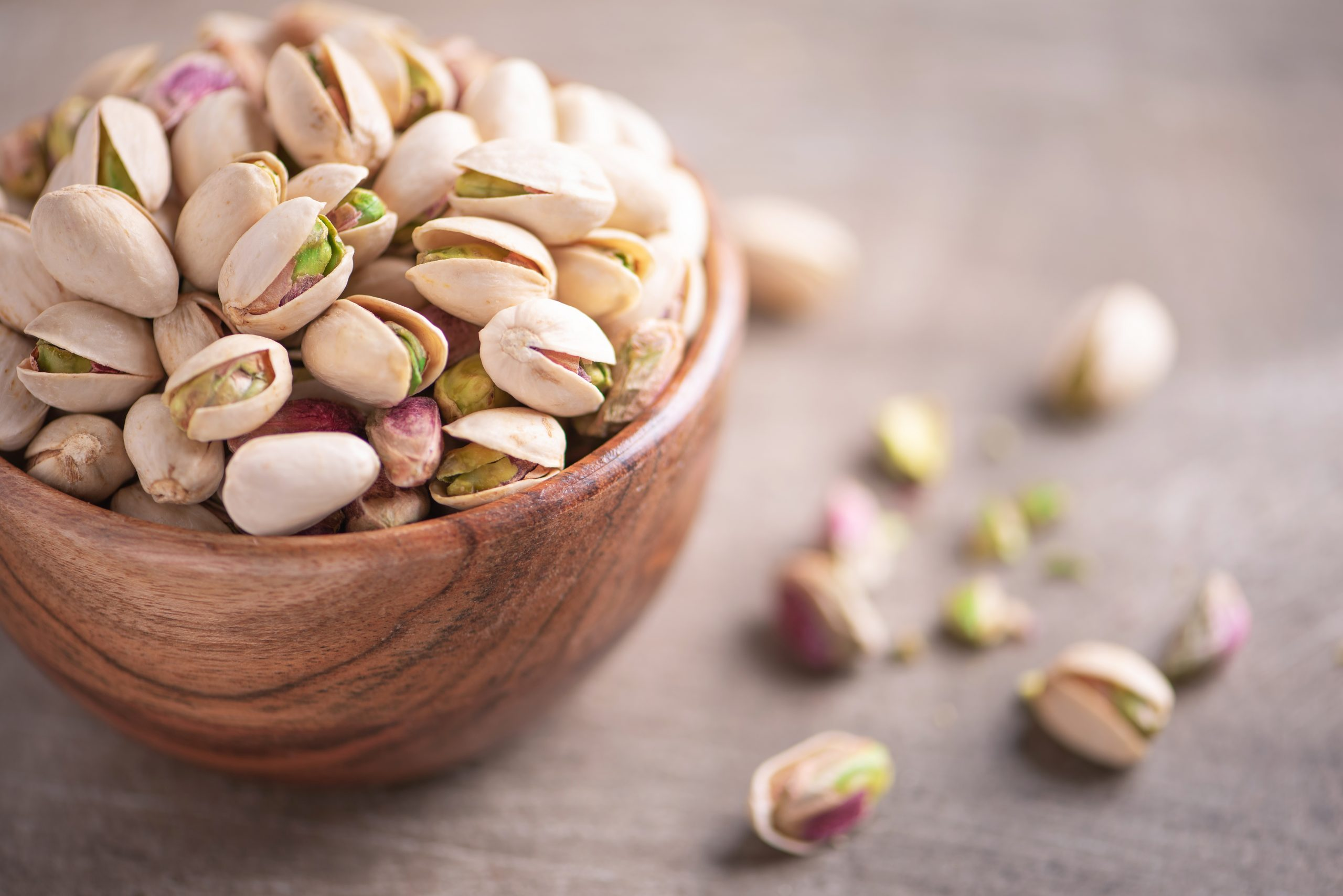 Green pistachio nuts in wooden bowl on wood textured background. Copy space. Superfood, vegan, vegetarian food concept. Macro of pistachio nut texture, selective focus. Healthy snack.