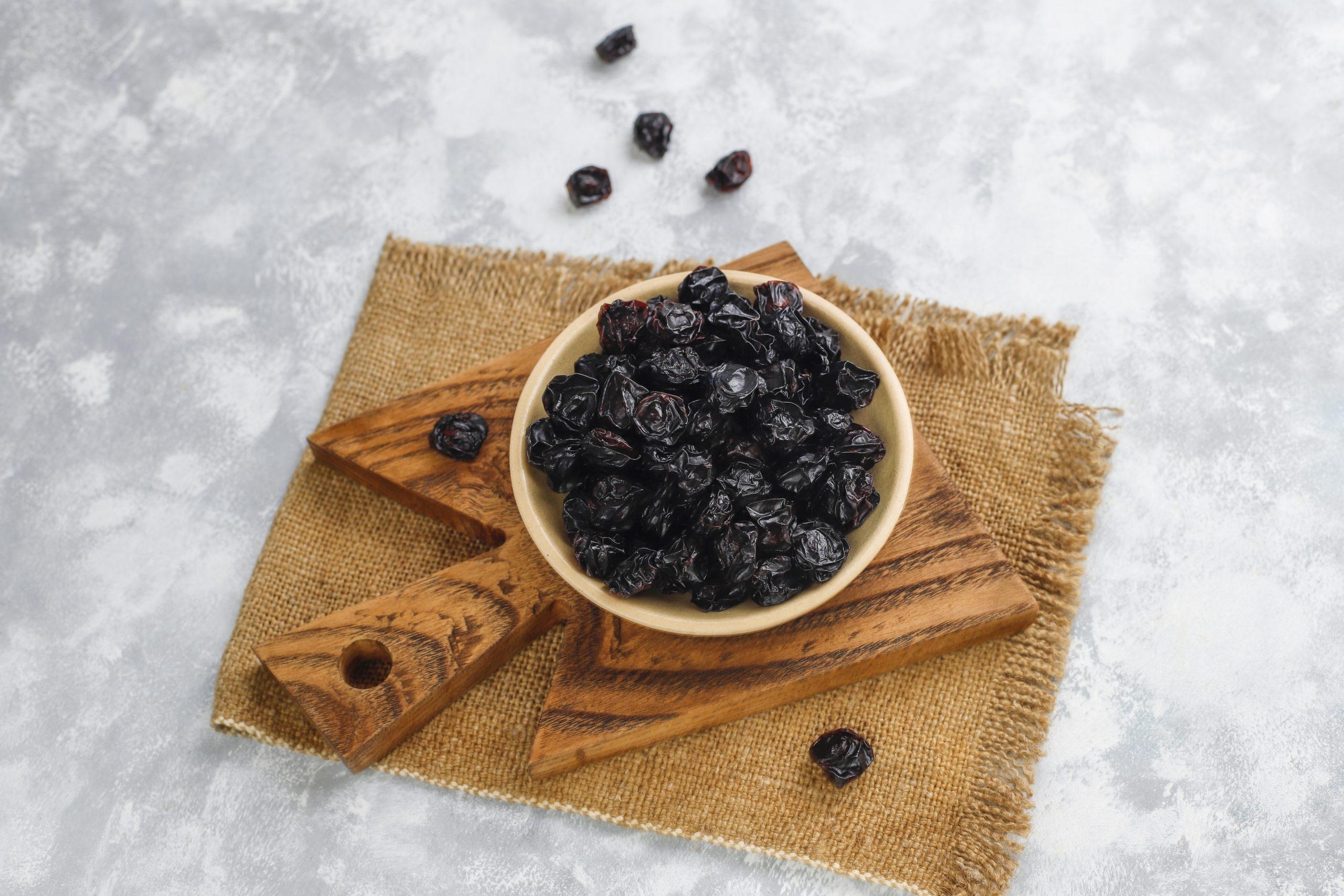 Organic raisins – dried plums on light background