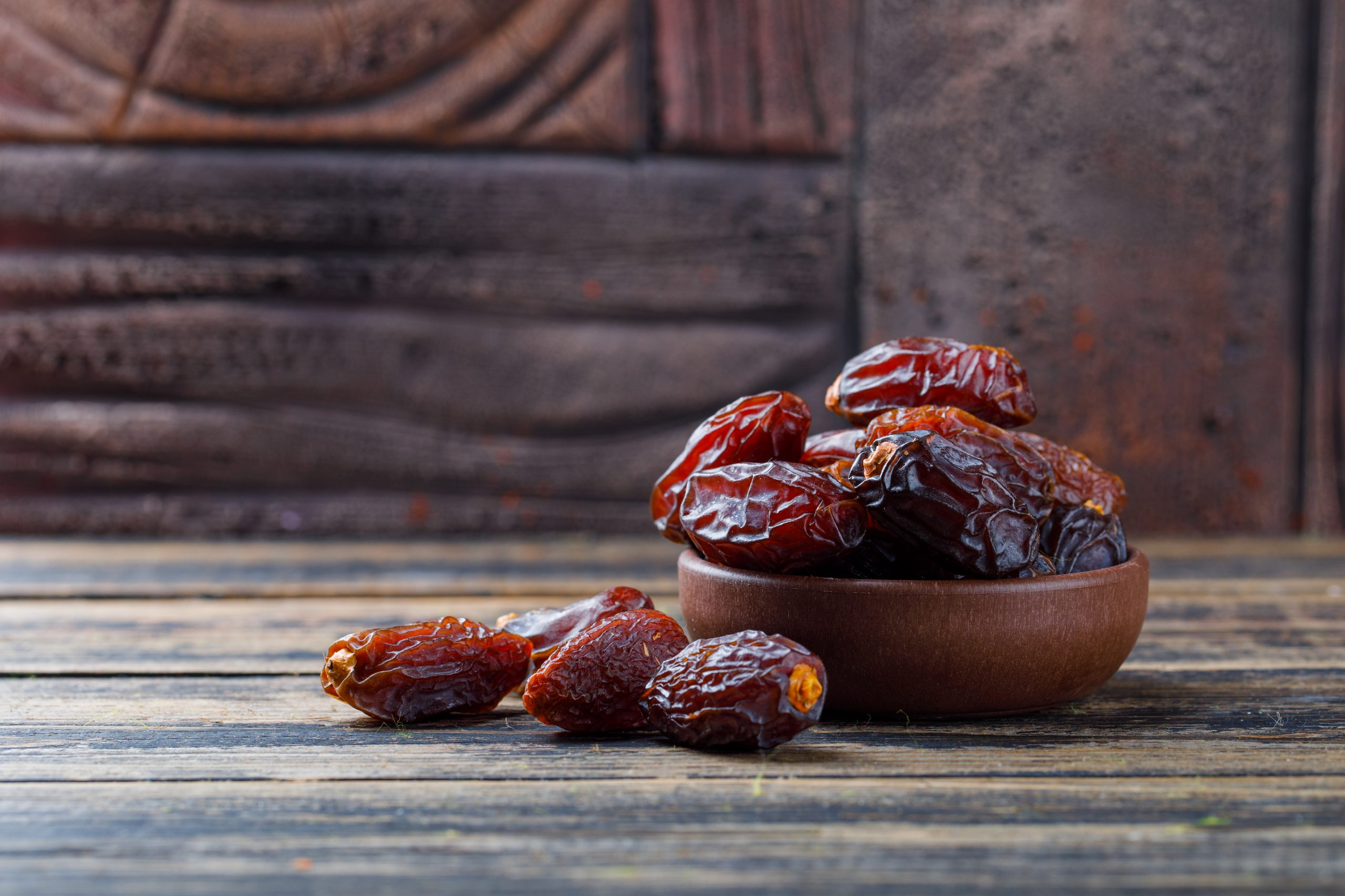 Sweet dates in a clay plate on stone tile and wooden background, side view.